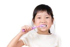 Piccoli denti asiatici della spazzola della ragazza Fotografia Stock
