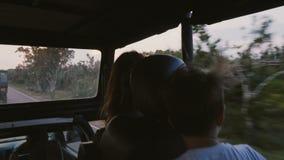 Piccoli famiglia, madre felice e ragazzino turistici, godenti del giro veloce di tramonto in automobile di escursione di safari l video d archivio