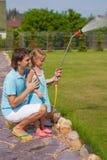 Piccoli fiori d'innaffiatura svegli del padre e della ragazza con Fotografia Stock