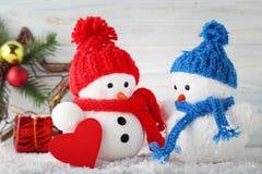 Piccoli giocattoli del pupazzo di neve con cuore immagini stock