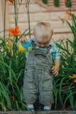 Piccoli giochi divertenti del ragazzo con la latta dell'acqua Fotografia Stock