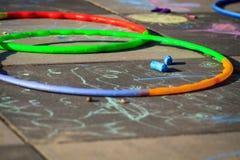 Piccoli hula-hoop del gioco della ragazza sul campo da giuoco fotografia stock