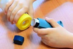 Piccoli inalatore e distanziatore di asma della tenuta del bambino in sue mani Farmaco e apparecchi medici Immagini Stock Libere da Diritti