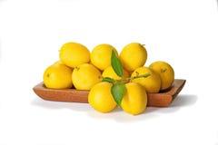 Piccoli limoni sul piatto i su bianco Immagine Stock