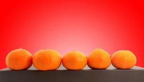 Piccoli mandarini del miele sparati sopra fondo rosso Immagine Stock