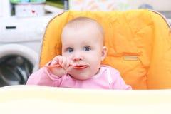 Piccoli 7 mesi felici di neonata con il cucchiaio sulla sedia del bambino nel kitc Fotografie Stock Libere da Diritti