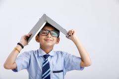 piccoli occhiali d'uso indiani/asiatici svegli del ragazzo di scuola con il libro sulla testa immagine stock