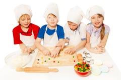 Piccoli panettieri svegli che preparano i biscotti riempiti caramella Fotografie Stock