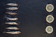 Piccoli pesci con il limone sulla tavola Immagini Stock