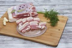 Piccoli pezzi tagliati di pancia di carne di maiale con aglio e pepe su un tagliere Pezzi succosi di bacon con pepe fotografia stock