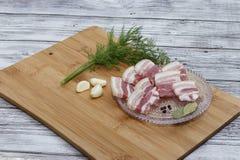 Piccoli pezzi tagliati di pancia di carne di maiale con aglio e pepe su un tagliere Pezzi succosi di bacon con pepe immagine stock