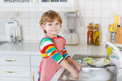 Piccoli piatti biondi felici di lavaggio del ragazzo del bambino in cucina domestica Fotografia Stock