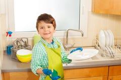 Piccoli piatti di lavaggio dell'assistente nella cucina Fotografie Stock
