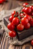 Piccoli pomodori ciliegia rossi su fondo rustico Pomodori di ciliegia sulla vite Fotografie Stock