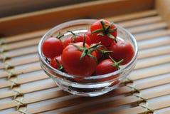 Piccoli pomodori ciliegia rossi in vetro Immagine Stock