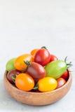 Piccoli pomodori ciliegia variopinti in ciotola di legno sulla tavola, verticale, spazio della copia Immagini Stock Libere da Diritti