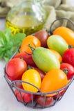 Piccoli pomodori ciliegia variopinti nel canestro del metallo, verticale Immagini Stock