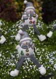 Piccoli pupazzi di neve piacevoli circondati dall'erba verde Fotografia Stock