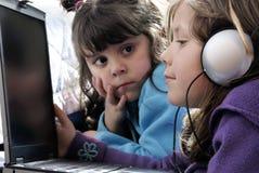 Piccoli ragazze e computer portatile fotografia stock