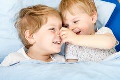 Piccoli ragazzi del fratello germano divertendosi a letto a casa Immagini Stock