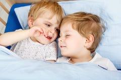 Piccoli ragazzi del fratello germano divertendosi a letto a casa Fotografia Stock