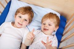 Piccoli ragazzi del fratello germano divertendosi a letto a casa Fotografia Stock Libera da Diritti