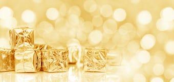Piccoli regali di Natale in carta brillante, fondo dorato di natale panoramico Fotografie Stock Libere da Diritti