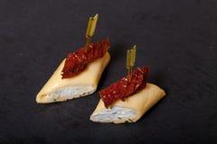 Piccoli rotoli con formaggio ed il pomodoro secco sullo spiedo su uno SL nero Fotografia Stock