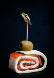 Piccoli rotoli con il salmone, il formaggio e la pita sullo spiedo su uno SL nero Fotografie Stock Libere da Diritti