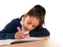 Piccoli scrittura del bambino femminile e compito ispanici fare con l'indicatore rosa Fotografie Stock