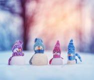 Piccoli snowmans su neve molle su fondo blu fotografia stock