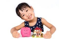 Piccoli soldi cinesi asiatici di risparmio della ragazza per il concetto della proprietà Immagine Stock