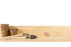 Piccoli strumenti di giardino accanto ai vasi della torba Immagine Stock