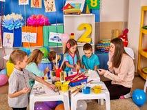 Piccoli studenti con la pittura dell'insegnante nella classe di scuola di arte Immagini Stock Libere da Diritti