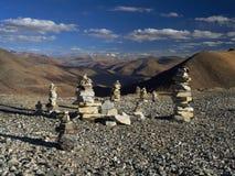 Piccoli stupas buddisti, composti di pietre grige alla cima della collina contro fondo delle alte montagne, un cielo blu con le n Fotografie Stock