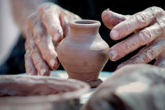 Piccoli vaso e mani di un vasaio Immagini Stock