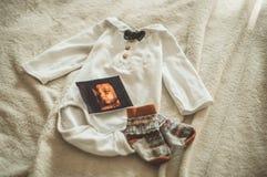 Piccoli vestiti fatti a mano del bambino Foto dell'ultrasuono vestiti neonati su fondo di lana beige fotografia stock