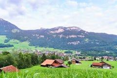 Piccoli villaggio e montagne svizzeri sull'orizzonte Immagine Stock