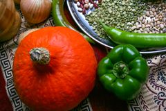 Piccoli zucca di Halloween e peperone verde gialli, cipolla, piselli, legumi sul piatto Vista superiore, fine su Fotografia Stock Libera da Diritti