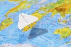 Piccolo aeroplano di carta sopra una mappa geografica del mondo Fuoco selettivo immagine stock