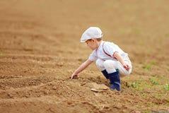 Piccolo agricoltore sveglio che spuding il suolo sul giacimento della molla Fotografia Stock