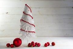 Piccolo albero di Natale bianco del cavo decorato con le bagattelle rosse e la b Fotografie Stock