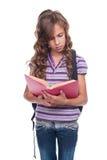 Piccolo allievo che legge libro interessante Immagine Stock