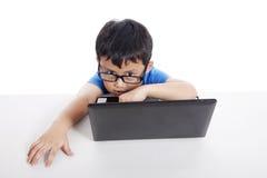 Piccolo allievo con il computer portatile Immagine Stock