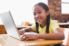 Piccolo allievo sveglio che esamina computer portatile in aula Immagini Stock