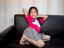 Piccolo allungamento asiatico del bambino della ragazza del bambino sul sofà Fotografia Stock