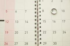 Piccolo anello d'argento messo sul calendario da tavolino Fotografie Stock Libere da Diritti