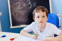 Piccolo 7 anni del ragazzo risolve la tavola di moltiplicazione Fotografie Stock Libere da Diritti