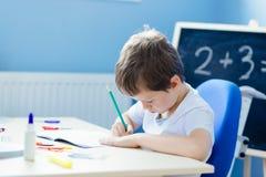 Piccolo 7 anni del ragazzo risolve la tavola di moltiplicazione Immagini Stock