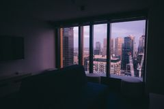 Piccolo appartamento con una grande finestra con una vista di un'architettura urbana della città fotografie stock